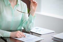 Biznesowej kobiety ręki w zielonym bluzki obsiadaniu przy biurkiem w biurze i egzamininują wynik finansowy dobro Fotografia Stock