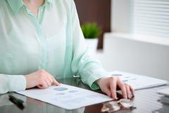 Biznesowej kobiety ręki w zielonym bluzki obsiadaniu przy biurkiem w biurze i egzamininują wynik finansowy dobro Zdjęcie Stock