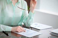 Biznesowej kobiety ręki w zielonym bluzki obsiadaniu przy biurkiem w biurze i egzamininują wynik finansowy dobro Obrazy Stock