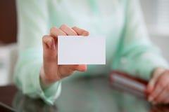 Biznesowej kobiety ręki w zielonym bluzki obsiadaniu przy biurkiem w biurze i trzymają out wizytówkę Zdjęcia Stock