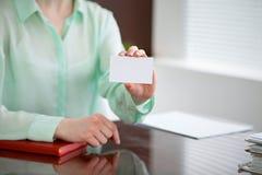 Biznesowej kobiety ręki w zielonym bluzki obsiadaniu przy biurkiem w biurze i trzymają out wizytówkę Obraz Royalty Free