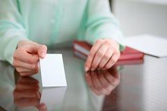 Biznesowej kobiety ręki w zielonym bluzki obsiadaniu przy biurkiem w biurze i trzymają out wizytówkę Zdjęcia Royalty Free