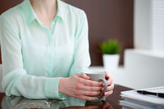 Biznesowej kobiety ręki w zielonym bluzki obsiadaniu przy biurkiem w biurze i trzymają szarą filiżankę, prawy okno Fotografia Royalty Free