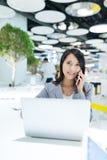 Biznesowej kobiety rozmowa telefon komórkowy i używać laptop Obraz Royalty Free
