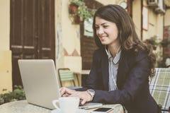 Biznesowej kobiety słuchająca muzyka i działanie na laptopie Zdjęcia Royalty Free