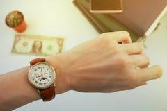 Biznesowej kobiety spojrzenia przy zegarkiem na jej nadgarstku nad białym stołem, na którym kłamamy pieniądze i dzienniczki fotografia royalty free