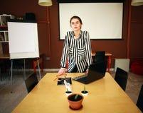 Biznesowej kobiety stojak w biurze z białej deski przedstawiać Fotografia Royalty Free