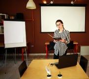 Biznesowej kobiety stojak w biurze z białej deski przedstawiać Zdjęcie Stock