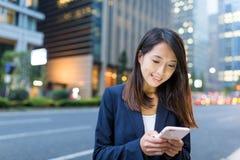 Biznesowej kobiety use telefon komórkowy w Tokio mieście przy nocą Fotografia Royalty Free