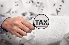 Biznesowej ręki podatku przyglądający słowo używać powiększać - szkło Fotografia Stock