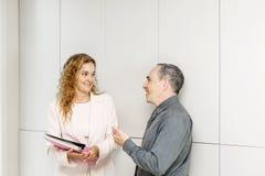 Biznesowi coworkers opowiada w korytarzu Obrazy Stock