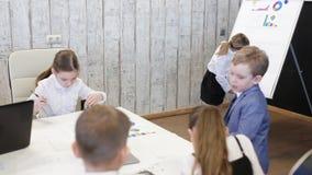 Biznesowi dzieci w kostiumach siedzą przy stołem w biurze zdjęcie wideo