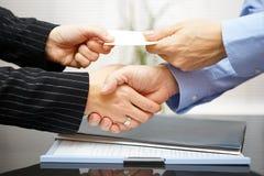 Biznesowi klienci wymieniają wizytówkę i handshakeing fotografia stock