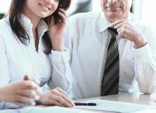 Biznesowi koledzy analizuje pieni??ne statystyki siedzi przy biurkiem fotografia royalty free