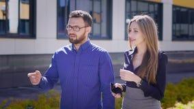 Biznesowi koledzy chodzą w biurze wpólnie po przerwa na lunch wzdłuż budynku w tle dwa kierownicy, zbiory wideo