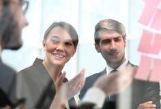 Biznesowi koledzy dyskutuje biznesowe notatki na szkle zdjęcia royalty free