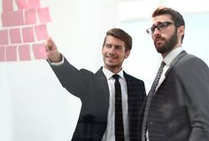 Biznesowi koledzy dyskutuje notatki na biuro desce zdjęcie royalty free