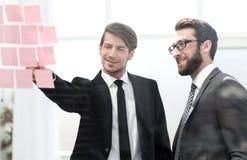 Biznesowi koledzy dyskutuje notatki na biuro desce fotografia stock