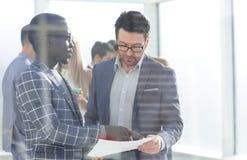 Biznesowi koledzy dyskutuje pracującego papier obraz stock