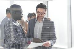 Biznesowi koledzy dyskutuje pracującego papier obrazy royalty free