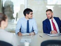Biznesowi koledzy Opowiada przy spotkanie stołem zdjęcia stock