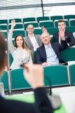 Biznesowi koledzy Podnosi ręki W Odczytowym Hall obraz stock