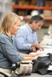 Biznesowi koledzy Pracuje Przy biurkiem W magazynie Zdjęcia Stock