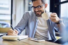 Biznesowi mężczyzna w błękitnej koszulowej pije kawie dla lunchu w kawiarni Zdjęcia Stock
