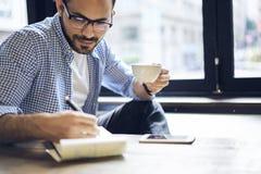 Biznesowi mężczyzna w błękitnym koszulowym działaniu wcześnie w ranku w kawiarni Zdjęcia Royalty Free