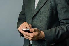 Biznesowi mężczyzna jest ubranym popielatą kurtkę i trzyma smartphone obrazy stock