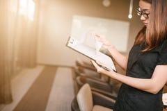 Biznesowi womanlooking smartphone i trzymać dokumenty w rękach Otwartej przestrzeni loft biuro, młoda biznesowa kobieta obraz stock