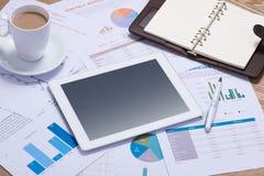 Biznesowi wykresy i mapy na drewnianym biurku z pastylką, kawa Obraz Royalty Free