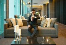 Biznesowy Azjatycki uśmiechnięty zegarek na kanapie w luxur i patrzeć zdjęcie stock