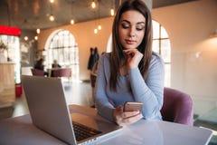 Biznesowy damy obsiadanie w kawiarni i działanie na używać telefonie i laptopie Zdjęcia Royalty Free