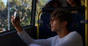 Biznesowy dojeżdżający opowiada na telefonie komórkowym podczas gdy podróżujący w autobusie 4k zdjęcie wideo