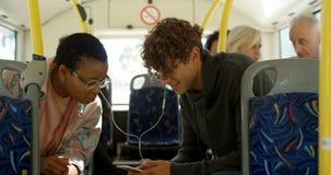 Biznesowy dojeżdżający opowiada na telefonie komórkowym podczas gdy podróżujący w autobusie 4k zbiory