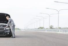 Biznesowy fachowy patrzeje awaria samochód na drodze przeciw niebu obrazy stock