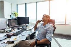 Biznesowy inwestor opowiada nad telefonem w biurze w szczęśliwym nastroju obraz royalty free