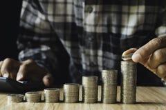 Biznesowy mężczyzna stawia monetę na monetach broguje oszczędzanie banka i uzasadnia jego pieniądze wszystko w finansowym księgow fotografia royalty free