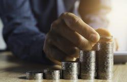 Biznesowy mężczyzna stawia monetę na monetach broguje oszczędzanie banka i uzasadnia jego pieniądze wszystko w finansowym księgow zdjęcia royalty free