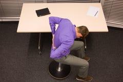 biznesowy mężczyzna ćwiczy przy biurkiem przy miejscem pracy Zdjęcia Royalty Free