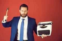 biznesowy mężczyzna, agresywny biznesmen z maszyna do pisania i młot, obrazy royalty free