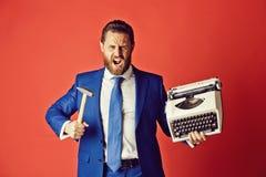 biznesowy mężczyzna, agresywny biznesmen z maszyna do pisania i młot, fotografia stock