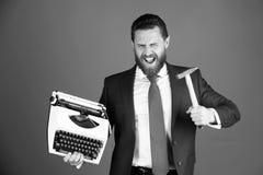 biznesowy mężczyzna, agresywny biznesmen z maszyna do pisania i młot, zdjęcia stock