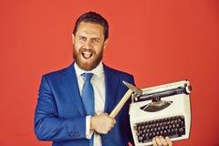 biznesowy mężczyzna, agresywny biznesmen z maszyna do pisania i młot, zdjęcia royalty free