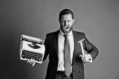 biznesowy mężczyzna, agresywny biznesmen z maszyna do pisania i młot, zdjęcie stock