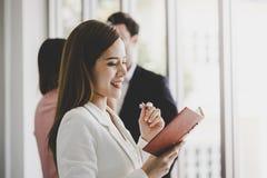 Biznesowy mężczyzna bierze notatkę przed dwa przyjaciół urzędnikiem w tle dla kobiety zaufania pojęcia obraz royalty free