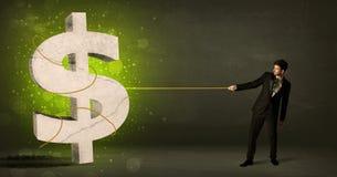 Biznesowy mężczyzna ciągnie dużego zielonego dolarowego znaka obraz stock
