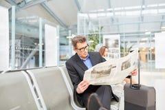 Biznesowy mężczyzna czyta gazetę przed jego podróżą służbową fotografia stock