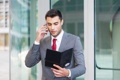 Biznesowy mężczyzna czyta jego agendę podczas gdy opowiadający na telefonie Obrazy Stock